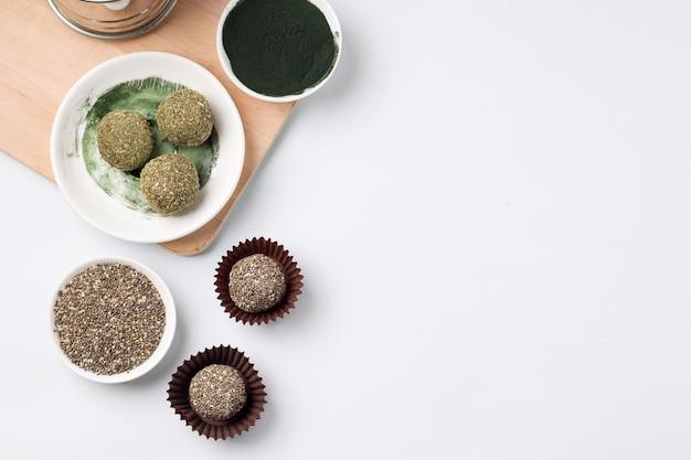 Gezonde zoete snoepjes van gedroogde vruchten energie ballen met munt en spirulina en chia zaden op een wit