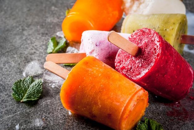 Gezonde zomerdesserts. ijslollys. bevroren tropische sappen, smoothies bosbessen. krenten, sinaasappel, mango, kiwi, banaan, kokosnoot, framboos. op zwarte stenen tafel copyspace