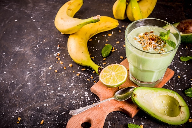 Gezonde zomerse drank, avocado en banaan smoothie met limoen, muesli en kokosmelk