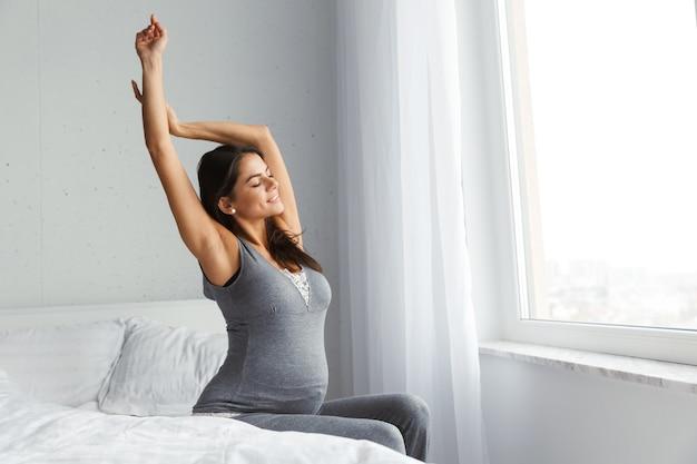 Gezonde zwangere vrouw binnenshuis thuis zitten poseren.