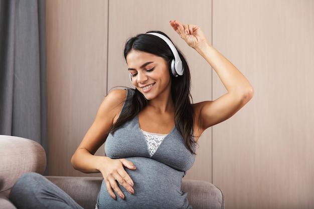 Gezonde zwangere vrouw binnenshuis thuis zittend op de bank luisteren muziek met een koptelefoon.