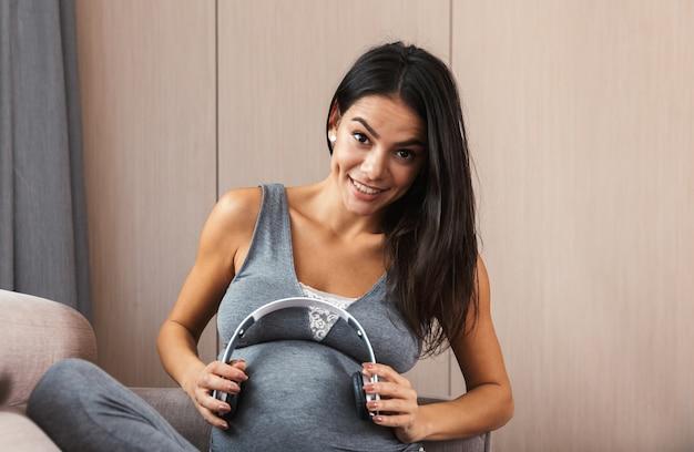 Gezonde zwangere vrouw binnenshuis thuis zittend op de bank met koptelefoon op buik.
