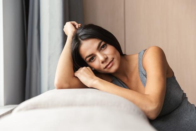 Gezonde zwangere vrouw binnenshuis thuis zittend op de bank.