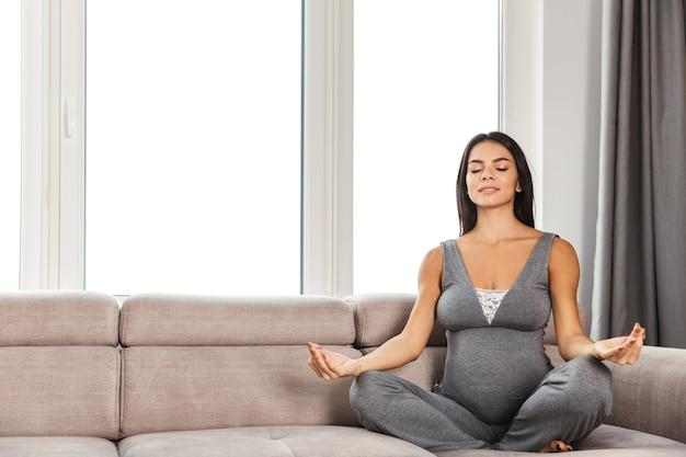 Gezonde zwangere vrouw binnenshuis zittend op de bank mediteren.