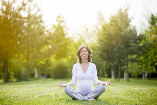Gezonde zwangere vrouw mediteren buitenshuis met gesloten ogen