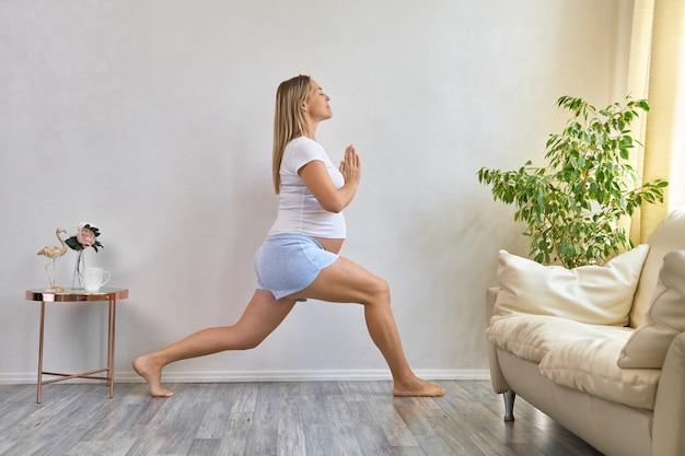 Gezonde zwangerschap yoga en fitness concept. jonge zwangere yogavrouw trainen in een gezellig woonkamerinterieur.