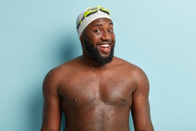 Gezonde zwarte man met atletische lichaamsvorm, die professionele zwemmer is, komt uit het water, voelt zich ontspannen en vol energie, draagt een badmuts, een veiligheidsbril, geïsoleerd op een blauwe muur