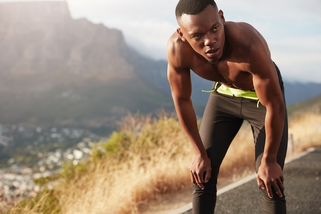 Gezonde zwarte mannelijke volwassene traint op bergweg, traint voor marathon, houdt beide handen op de knieën, kijkt bedachtzaam in de verte, rent op het platteland, heeft vastberaden gezichtsuitdrukking.