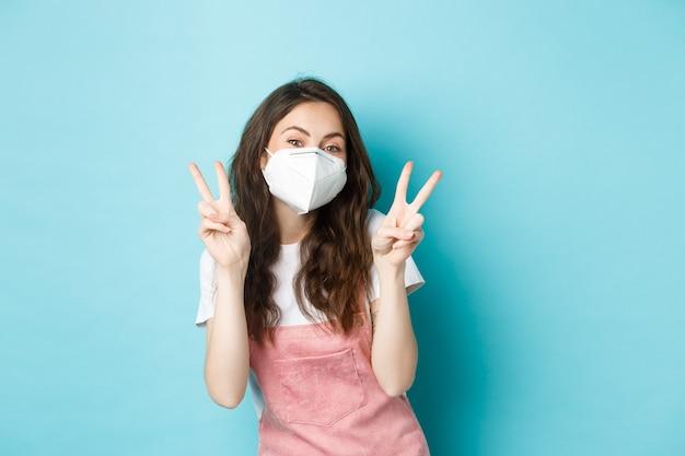 Gezondheid, coronavirus en social distancing concept. gelukkige jonge vrouw in medisch gasmasker die v-tekens toont. schattig meisje poseren in gezichtsmasker met vredesgebaar, blauwe achtergrond