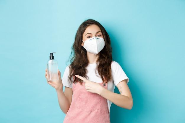 Gezondheid, coronavirus en social distancing concept. jonge vrouw met gezichtsmasker, gasmasker dragend en wijzend op handdesinfecterend middel, antiseptische, blauwe achtergrond aanbevelend