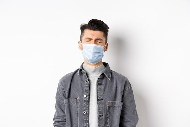 Gezondheid, covid en pandemie concept. triest huilende man in medisch masker boos over quarantaine, staande op een witte achtergrond.