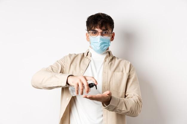 Gezondheid, covid en quarantaineconcept. jonge spaanse man in glazen en gezichtsmasker met handdesinfecterend middel, antisepticum toepassen en kijken, staande op een witte muur.