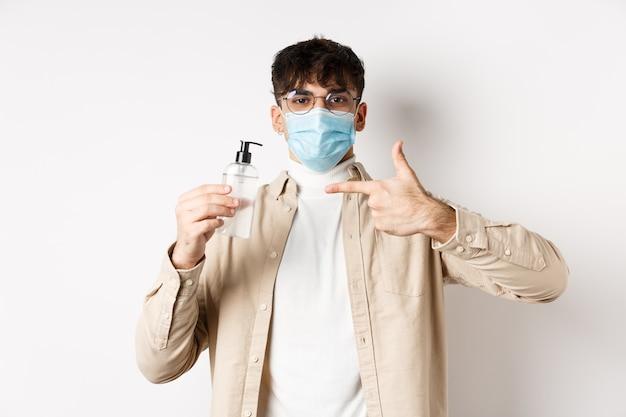 Gezondheid, covid en quarantaineconcept. vrolijke jonge kerel in gezichtsmasker glazen wijzende vinger naar fles antisepticum, met goede handdesinfecterend middel, witte muur.