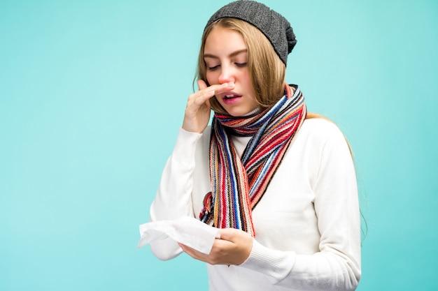 Gezondheid en geneeskunde concept - sad teen girl blaast neus in weefsel, op een blauwe achtergrond. mooi meisje koud van snot. - afbeelding