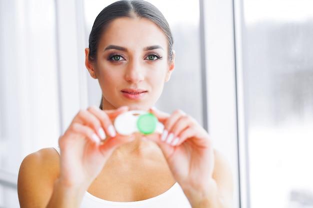 Gezondheid en geneeskunde. een mooie jonge oogarts met een glimlach houdt een contactlenscontainer vast. oog zorg. gezonde visie. meisje met groene ogen. hoge resolutie