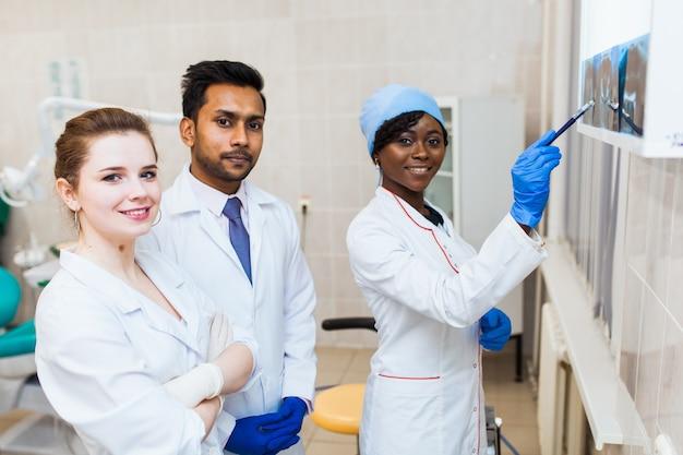 Gezondheid en gezondheidszorg. een multinationale groep tandartsen onderzoekt röntgenfoto's in aanwezigheid van een patiënt. praktijk aan een medische universiteit.
