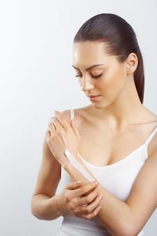 Gezondheid en lichaamsverzorging thema mooie vrouwelijke hand met witte crème geïsoleerd op een witte achtergrond