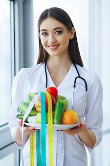 Gezondheid en schoonheid. ernstige arts schrijft vliegtuigdieet. vrouw zit op kantoor. jonge dokter met mooie glimlach en vers fruit.
