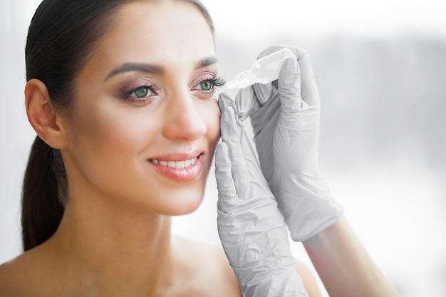 Gezondheid en schoonheid. oog zorg. mooie jonge vrouw met druppels voor ogen. goed zicht. gelukkig meisje met frisse look