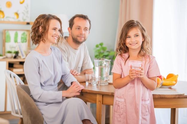 Gezondheid en schoonheidsconcept - glimlachend meisje dat een glas water houdt. gelukkige ouders op de achtergrond.