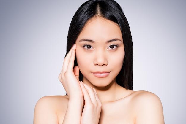 Gezondheid en welzijn. portret van een mooie jonge en shirtloze aziatische vrouw die haar gezicht aanraakt terwijl ze tegen een grijze achtergrond staat