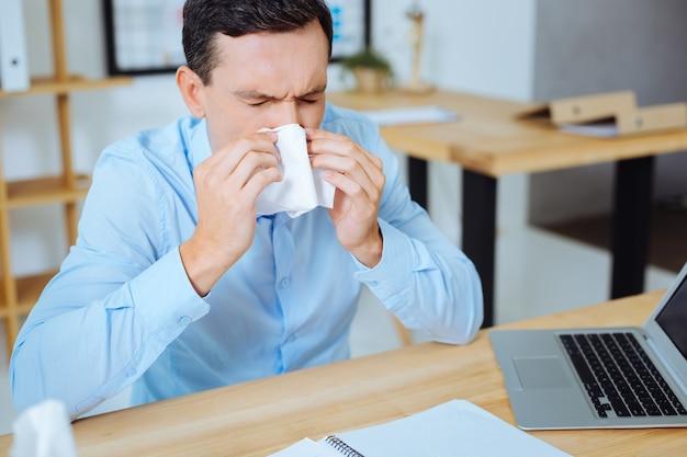 Gezondheid. gefrustreerde man zit op zijn werkplek en zet ellebogen op tafel terwijl hij de ogen gesloten houdt