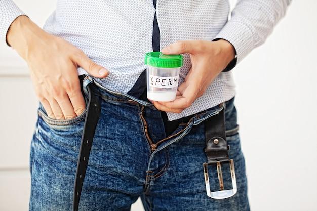 Gezondheid. monster sperma. donorsperma sluit concept banksperma. onvruchtbaarheid een man die in handen container met sperma