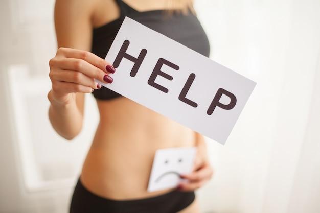 Gezondheid van de vrouw. vrouwelijke lichaam holding symbool help-kaart in de buurt van maag