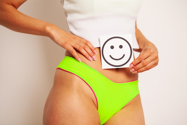 Gezondheid van vrouwen, mooi vrouwelijk lichaam in slipje met glimlach-kaart.