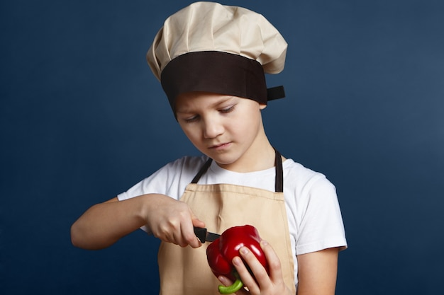 Gezondheid, voeding en eten. foto van ernstige geconcentreerde kleine jongen in chef-kok glb staande op blinde muur en rode peper met mes pellen tijdens het koken van gezond diner of lunch met verse groenten