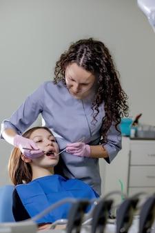 Gezondheids controle. tandarts in het stomatologiecentrum maakt een onderzoek van vrouwentanden met behulp van tandheelkundige instrumenten.