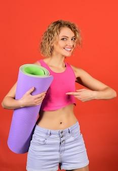 Gezondheids- en lichaamsverzorging sportconcept gelukkige fitnessvrouw houdt yogamat vast en toont vingersportvrouw