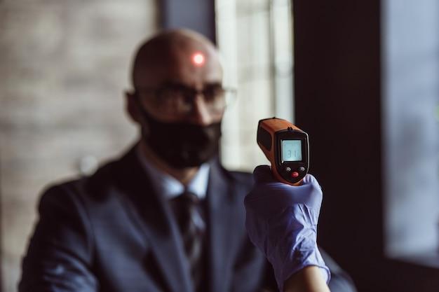 Gezondheidsambtenaar die de temperatuur van een zakenman in de ingang van het zakencentrum controleert