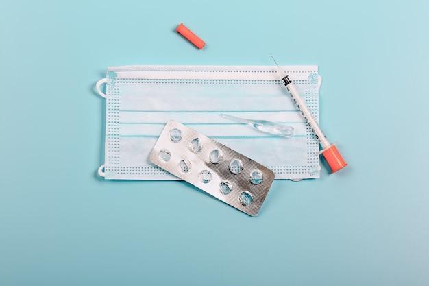 Gezondheidsbescherming en geneeskunde medisch masker blister van pillen ampul spuit op een blauwe achtergrond sp...