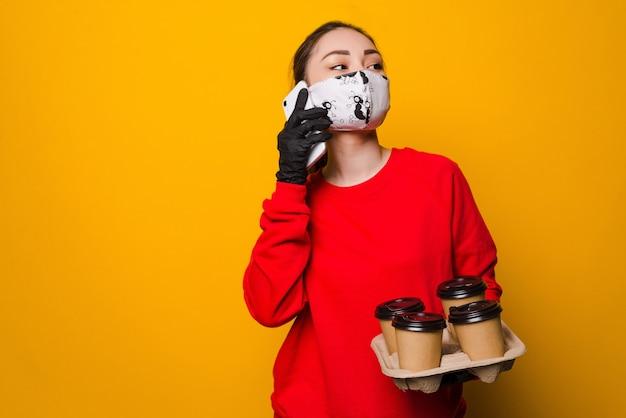 Gezondheidsbescherming, veiligheid en pandemie concept. levering aziatische vrouw praten via de telefoon in beschermend gezichtsmasker en handschoenen