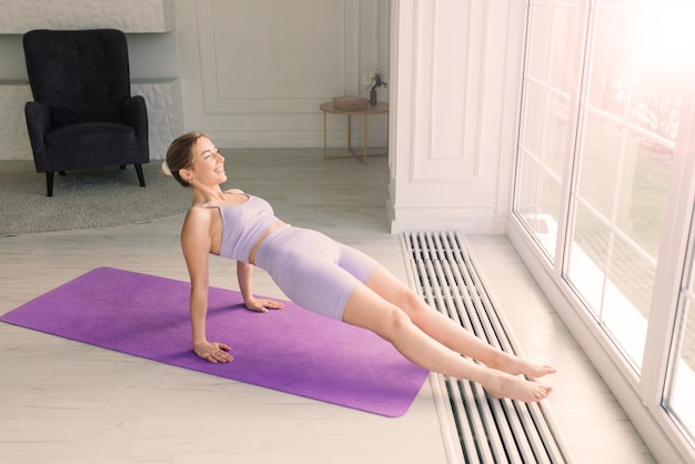 Gezondheidsconcept. jonge mooie vrouw doet yoga-oefening in de moderne kamer