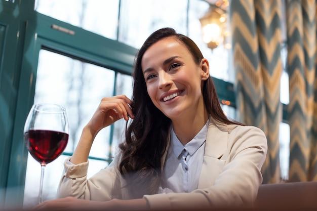 Gezondheidseffecten van wijn. lage hoek van vrolijke vrolijke aardige vrouw grijnzend terwijl het aanraken van glas wijn en haar strelen