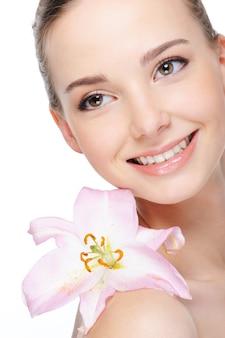 Gezondheidskleur van mooie gelukkige lachende jonge vrouw met lelie op haar naakte schouder