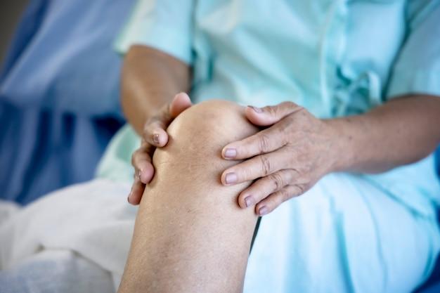 Gezondheidsprobleem concept; oude vrouw die lijdt aan kniepijn in het ziekenhuis.