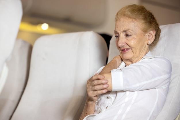 Gezondheidsprobleem in een vliegtuig. de oudere vrouwelijke passagier in het vliegtuig voelde schouderpijn van een lange vliegreis