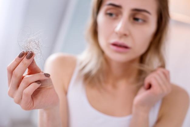 Gezondheidsproblemen. droevige ongelukkige vrouw die haar haar bekijkt terwijl zij aan een ziekte lijdt
