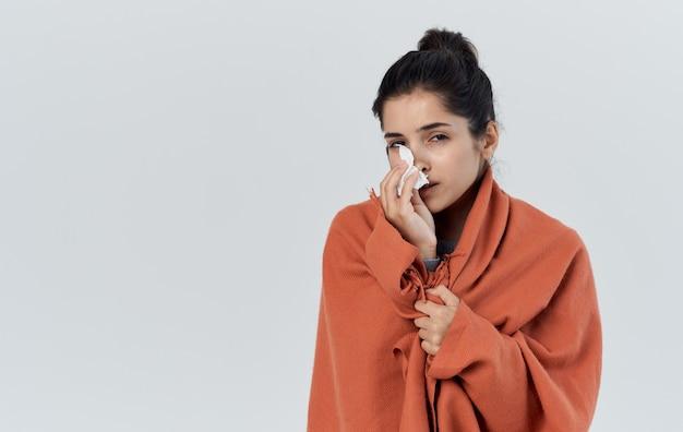 Gezondheidsproblemen mooie vrouw oranje plaid in licht servetmodel als achtergrond. hoge kwaliteit foto