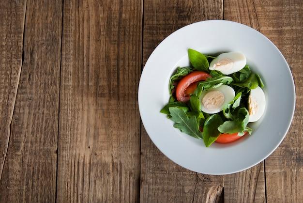 Gezondheidssalade met gekookte eieren, tomaat, sla, rucola en spinazie.