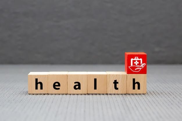 Gezondheidstekst op houten stuk speelgoed blokken die met geneeskundezak worden gestapeld. concepten een lichamelijk onderzoek voor gezondheidszorg en ziektekostenverzekering.