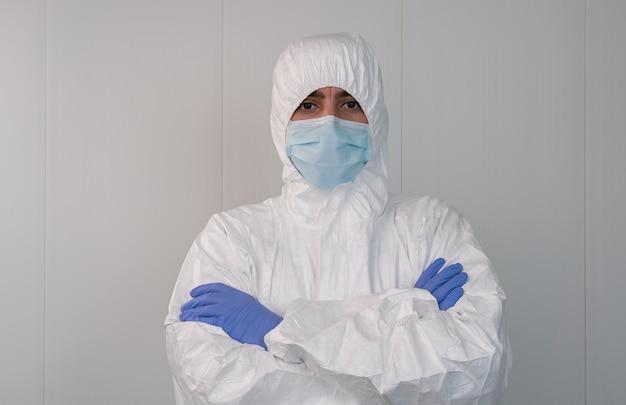 Gezondheidswerker in een beschermend pak kruist zijn armen in het ziekenhuis