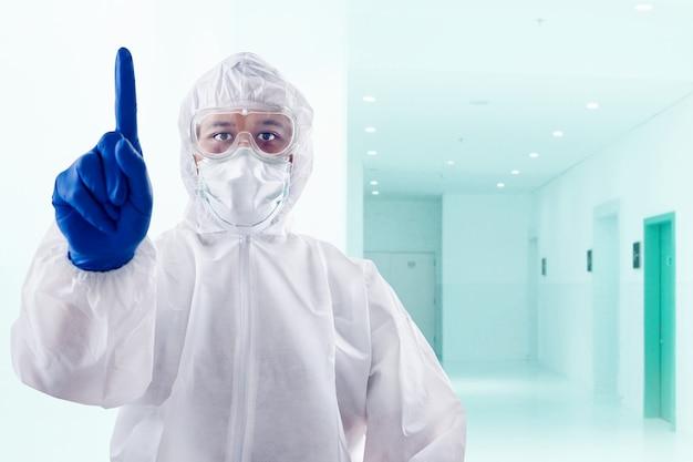Gezondheidswerker met een beschermend pak en handschoenen die met een naar boven wijzend gebaar op het ziekenhuis staan