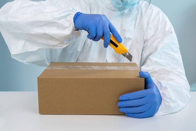 Gezondheidswerker op persoonlijke beschermingsmiddelen uitpakken van een doos met chirurgische maskers in het ziekenhuis. verpleger draagt handhandschoenen te midden van de coronavirus-epidemie