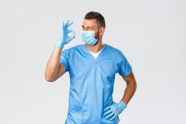 Gezondheidswerkers, covid-19, coronavirus en preventie van virusconcept. brutale knappe dokter in scrubs en medisch masker, garandeer de beste servicekwaliteit, garandeer, toon oké teken en knipoog