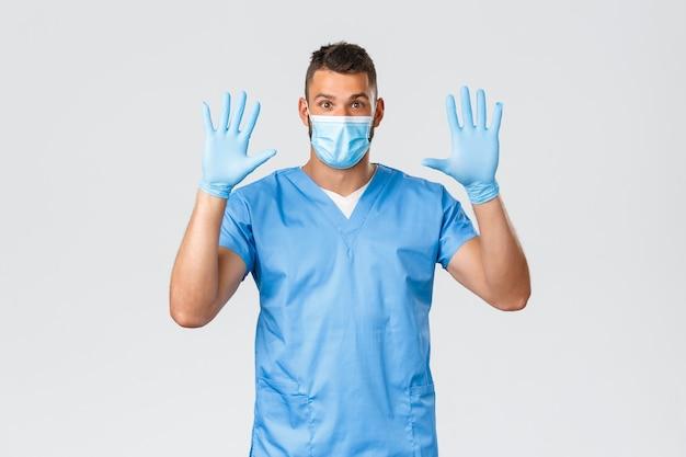 Gezondheidswerkers, covid-19, coronavirus en preventie van virusconcept. opgewonden glimlachende mannelijke arts, verpleegster met medisch masker en handschoenen, handen opstekend, draag rubberen handschoenen, grijze achtergrond