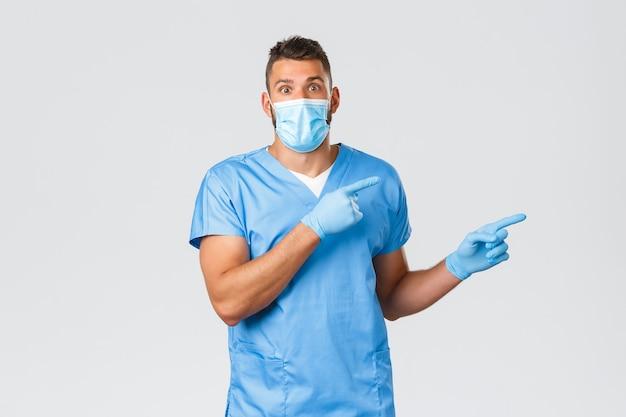 Gezondheidswerkers, covid-19, coronavirus en preventie van virusconcept. verrast en opgewonden verpleger, arts met medisch masker en scrubs, wijzende vingers naar rechts en goed nieuws vertellend, kijk verbaasd